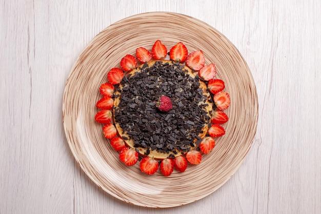 Vista superior de deliciosas panquecas assadas com morangos e gotas de chocolate na mesa branca