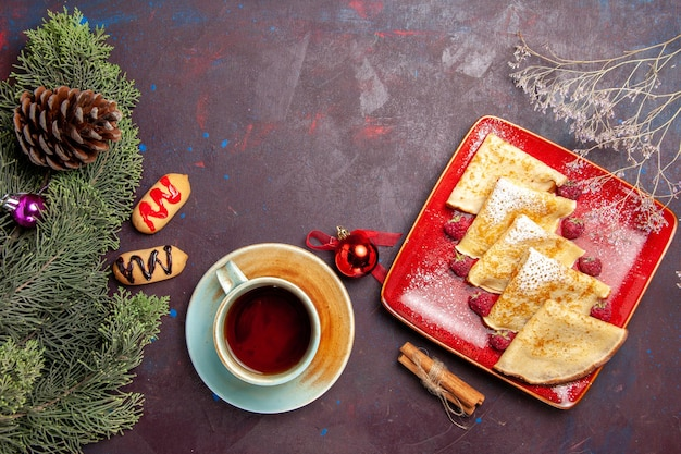 Vista superior de deliciosas panquecas doces com framboesas e chá na mesa preta