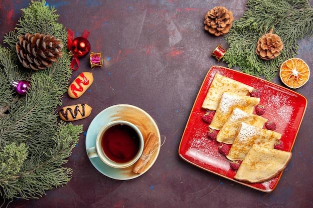 Vista superior de deliciosas panquecas doces com framboesas e uma xícara de chá no preto