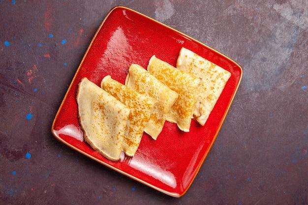 Vista superior de deliciosas panquecas doces dentro de um prato vermelho no escuro