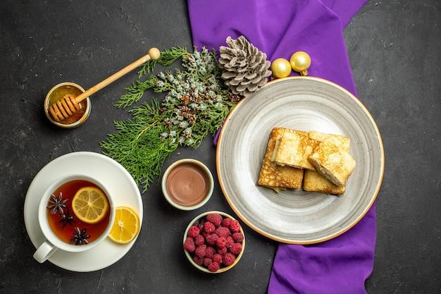 Vista superior de deliciosas panquecas em um prato branco, acessórios de decoração de chocolate e framboesa na toalha roxa e uma xícara de chá preto no fundo preto