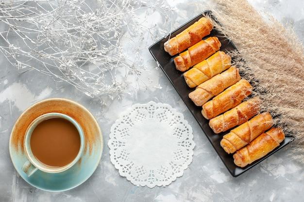 Vista superior de deliciosas pulseiras assadas dentro de mofo preto com café com leite em cinza, pastelaria