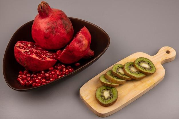 Vista superior de deliciosas romãs cortadas ao meio e inteiras em uma tigela com fatias de kiwi em uma placa de cozinha de madeira