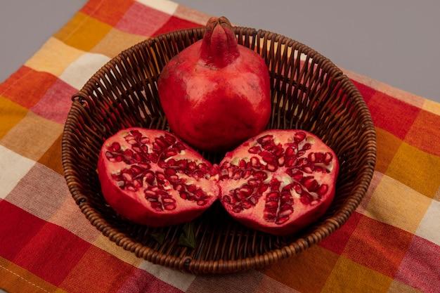 Vista superior de deliciosas romãs vermelhas e suculentas em um balde em um pano xadrez