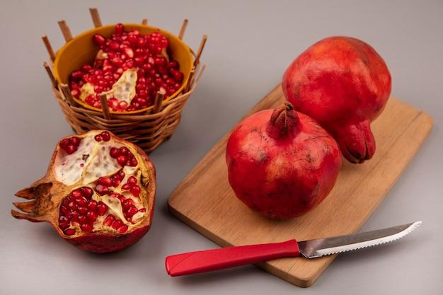 Vista superior de deliciosas romãs vermelhas em uma placa de cozinha de madeira com uma faca com sementes de romã em uma tigela