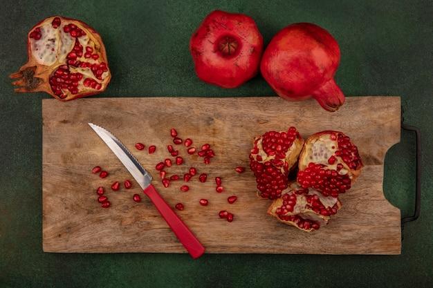 Vista superior de deliciosas sementes de romã em uma placa de cozinha de madeira com uma faca com romãs inteiras isoladas