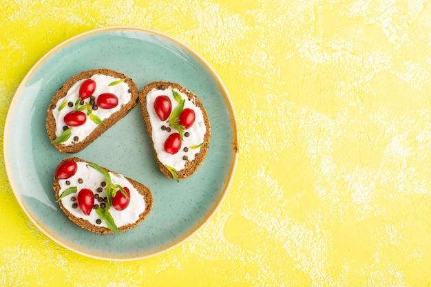 Vista superior de deliciosas torradas de pão com creme de leite e dogwoods dentro de um prato azul na superfície amarelaç