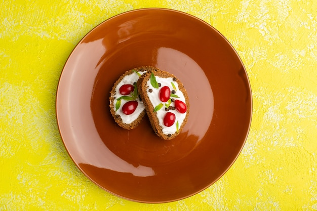 Vista superior de deliciosas torradas de pão com creme de leite e dogwoods dentro de um prato marrom na mesa amarela