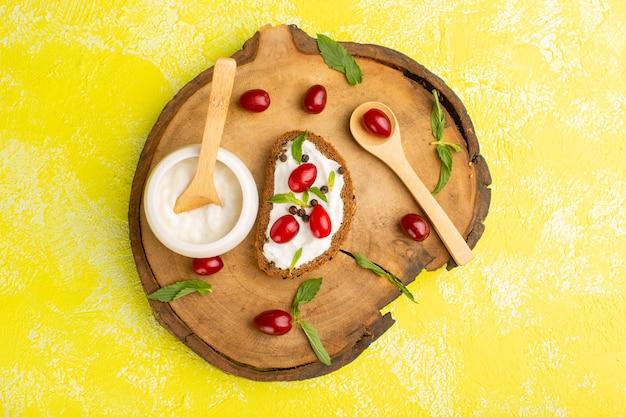 Vista superior de deliciosas torradas de pão com creme de leite e dogwoods em toda a superfície amarela