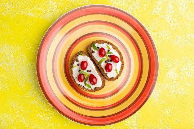 Vista superior de deliciosas torradas de pão com creme de leite e dogwoods
