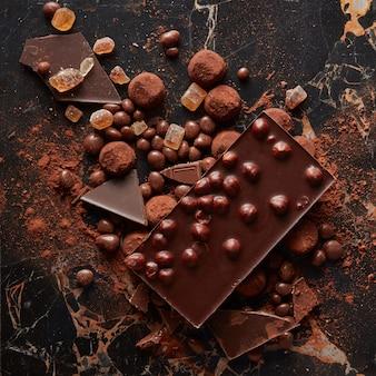 Vista superior de deliciosas trufas de chocolate e doces no cacau em pó na superfície de mármore