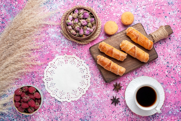 Vista superior de deliciosos bagels com uma xícara de chá e frutas na superfície rosa claro