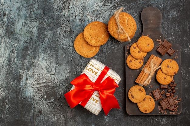 Vista superior de deliciosos biscoitos, barras de chocolate e caixa de presente em um fundo escuro de gelo