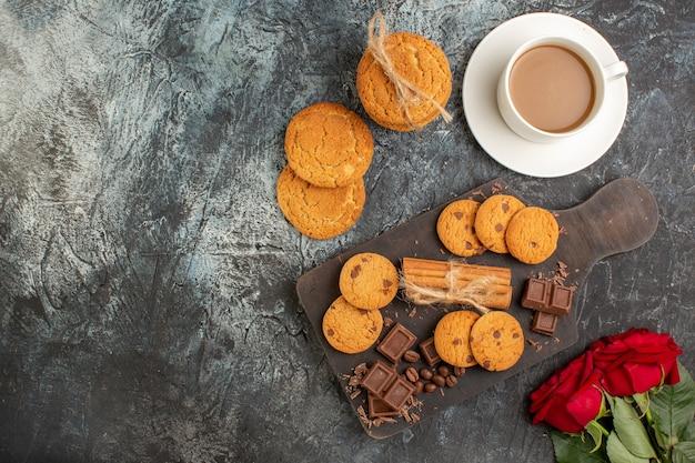 Vista superior de deliciosos biscoitos, barras de chocolate, rosas vermelhas e uma xícara de café no lado esquerdo em um fundo escuro e gelado