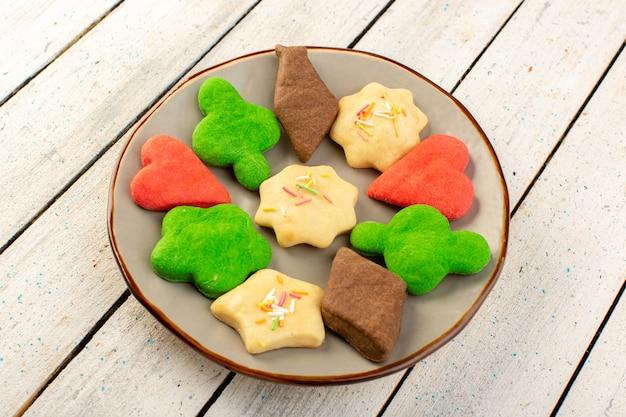 Vista superior de deliciosos biscoitos coloridos diferentes formados dentro da placa redonda sobre o chá de açúcar doce de biscoito de mesa de madeira cinza