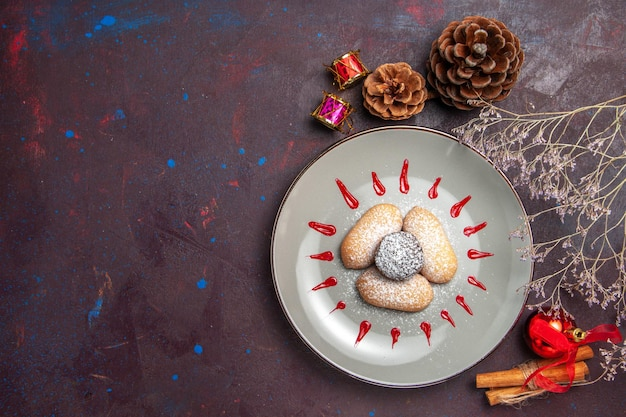 Vista superior de deliciosos biscoitos com cobertura vermelha no preto