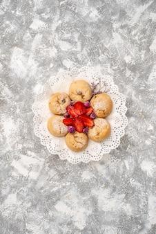 Vista superior de deliciosos biscoitos de açúcar com morangos na superfície branca