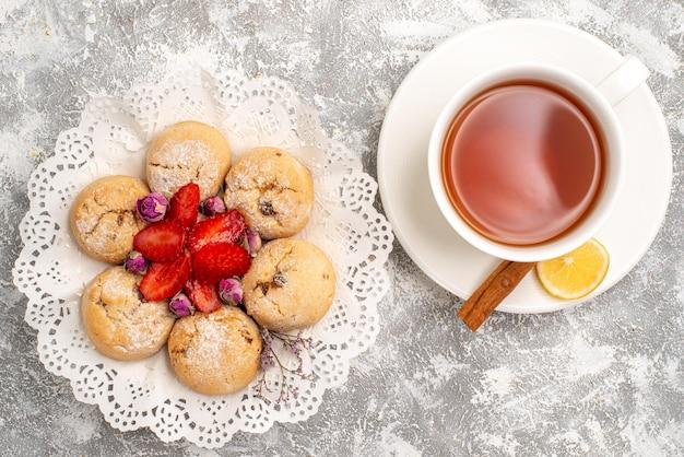 Vista superior de deliciosos biscoitos de areia com morangos frescos e uma xícara de chá em uma superfície branca clara