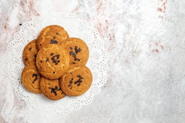 Vista superior de deliciosos biscoitos de areia, doces perfeitos para uma xícara de chá na superfície branca