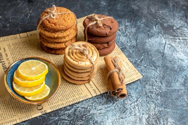 Vista superior de deliciosos biscoitos de canela e limão empilhados em um jornal velho sobre fundo escuro