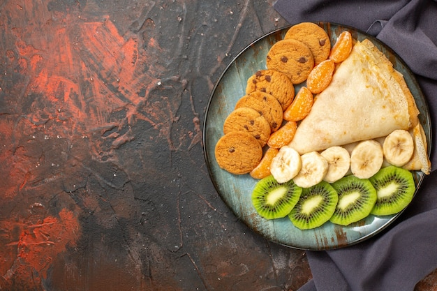 Vista superior de deliciosos biscoitos de crepe de frutas cítricas picados em uma toalha escura em cores diferentes