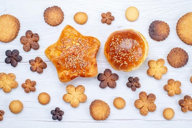 Vista superior de deliciosos biscoitos doces diferentes formados junto com bolos assados na mesa leve, biscoito doce com açúcar