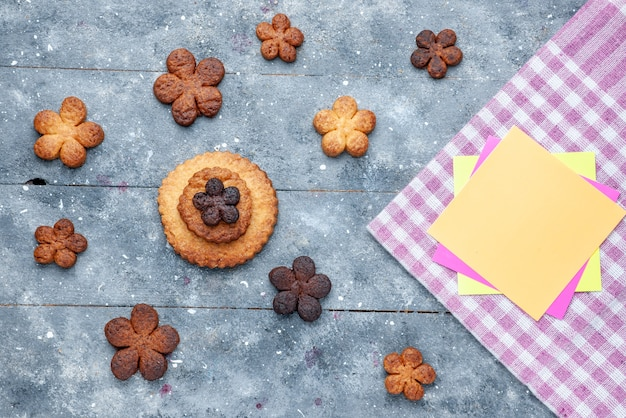 Vista superior de deliciosos biscoitos doces espalhados por toda a mesa cinza de madeira, biscoito doce, biscoito doce