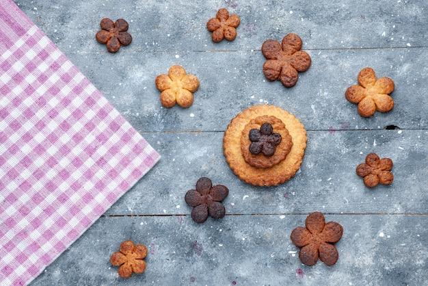 Vista superior de deliciosos biscoitos doces espalhados por todo o cinza de madeira, biscoito de açúcar e biscoito doce