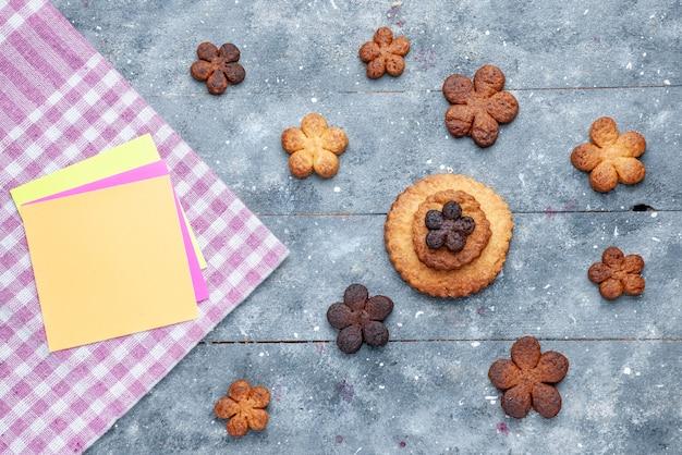 Vista superior de deliciosos biscoitos doces espalhados por todo o cinza de madeira, biscoito doce