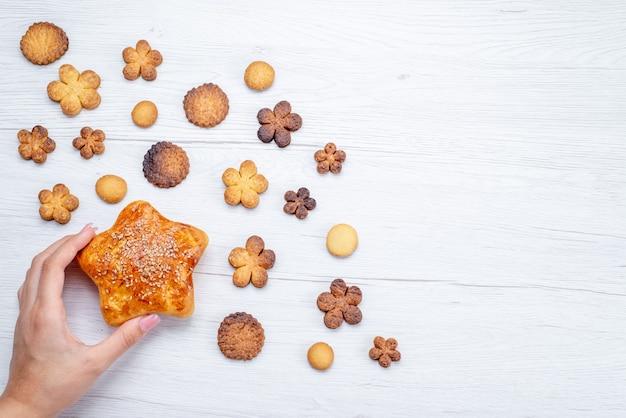 Vista superior de deliciosos biscoitos doces formados de forma diferente junto com massa assada na luz, biscoito de biscoito doce com açúcar