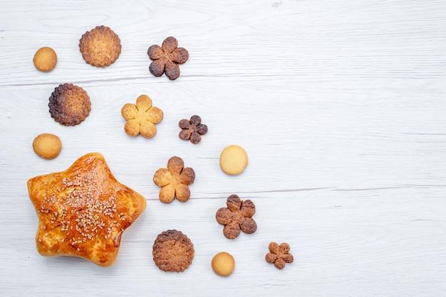 Vista superior de deliciosos biscoitos doces formados de forma diferente junto com massa assada na mesa leve, biscoito doce com açúcar