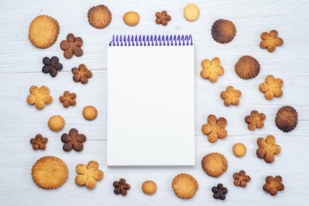 Vista superior de deliciosos biscoitos doces formados de forma diferente junto com o bloco de notas na mesa leve