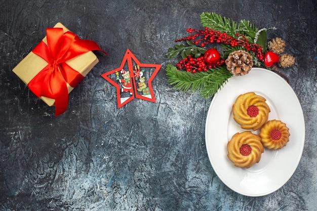 Vista superior de deliciosos biscoitos em um prato branco e um presente de decoração de ano novo com fita vermelha na superfície escura