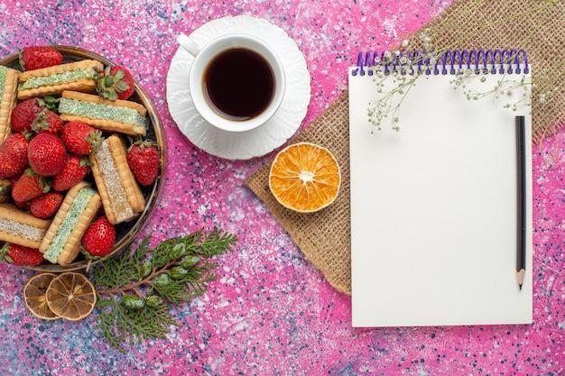 Vista superior de deliciosos biscoitos waffle com morangos vermelhos frescos e chá na superfície rosa