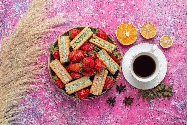 Vista superior de deliciosos biscoitos waffle com morangos vermelhos frescos e uma xícara de chá na superfície rosa