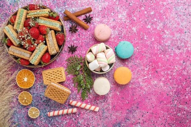 Vista superior de deliciosos biscoitos waffle com morangos vermelhos frescos na superfície rosa