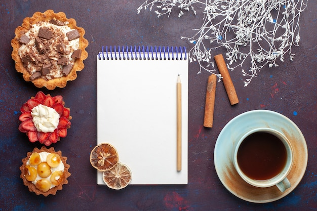 Vista superior de deliciosos bolos com creme de chocolate e frutas com bloco de notas de chá na superfície escura