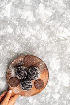 Vista superior de deliciosos bolos de bolas de chocolate com biscoitos em uma superfície branca clara