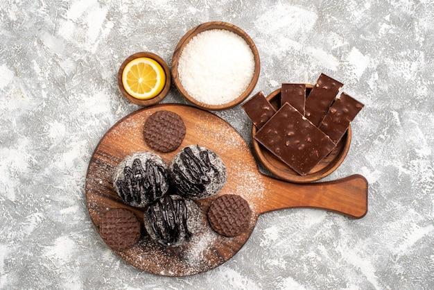 Vista superior de deliciosos bolos de bolas de chocolate com biscoitos na superfície branca