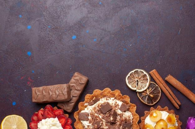 Vista superior de deliciosos bolos junto com canela e doces na superfície escura