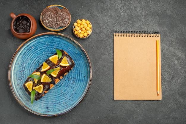 Vista superior de deliciosos bolos na bandeja azul e biscoitos com o caderno na mesa escura