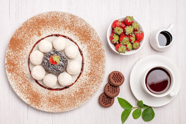 Vista superior de deliciosos bombons de coco com bolo de chocolate e xícara de chá em branco