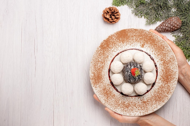 Vista superior de deliciosos doces de coco com bolo de cacau em branco