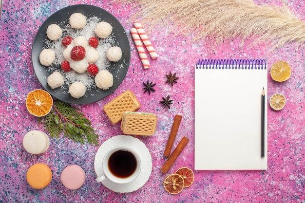 Vista superior de deliciosos doces de coco com morangos frescos e waffles na superfície rosa