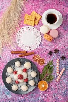 Vista superior de deliciosos doces de coco com morangos vermelhos frescos na superfície rosa