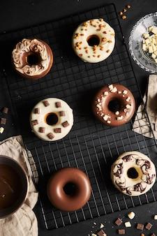 Vista superior de deliciosos donuts com cobertura de chocolate em uma bandeja
