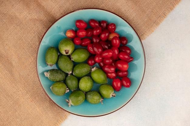 Vista superior de deliciosos feijoas maduros com cerejas da cornalina em um prato azul em um pano de saco sobre uma superfície cinza