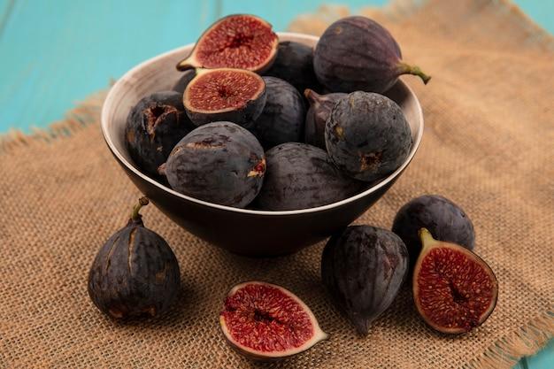 Vista superior de deliciosos figos pretos maduros da missão em uma tigela sobre um pano de saco na parede azul