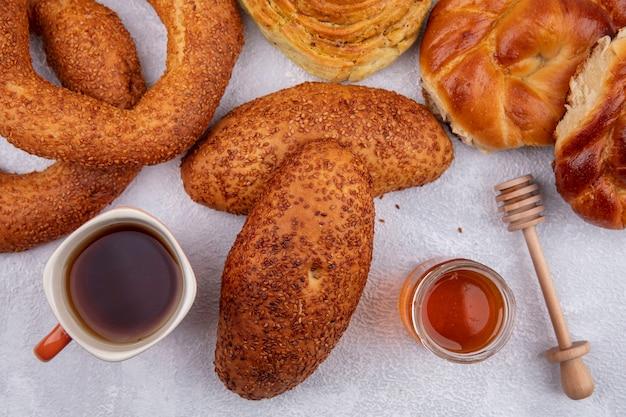 Vista superior de deliciosos hambúrgueres de gergelim com uma xícara de chá e mel em uma jarra de vidro e diferentes pães isolados em um fundo branco