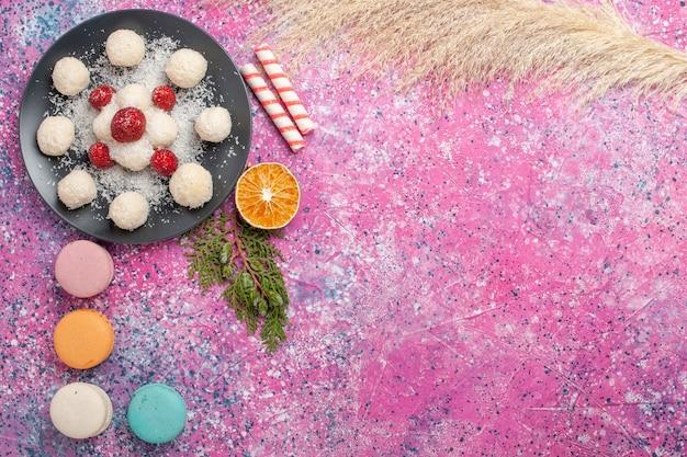 Vista superior de deliciosos macarons franceses com bombons de coco na superfície rosa